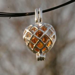 Wunderschöner, aufklappbarer Herzanhänger mit kognacfarbener Bernsteinperle hinter Gittern