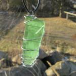 Grosser Anhänger aus grünem Seeglas in einer Spirale