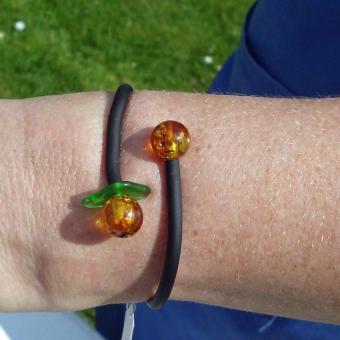Flexibles Kautschukarmband mit 2 polierten Bernsteinperlen und grünem Seeglas